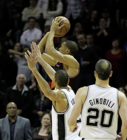 Spurs' Tim Duncan (21) attempts to cover Phoenix Suns' Wesley Johnson (02) as he shoots a three-pointer to send the game into overtime in the closing moments of the fourth quarter at the AT&T Center on Wednesday, Feb. 27, 2013. Suns defeated the Spurs, 105-101, in overtime. Photo: Kin Man Hui, San Antonio Express-News / © 2012 San Antonio Express-News