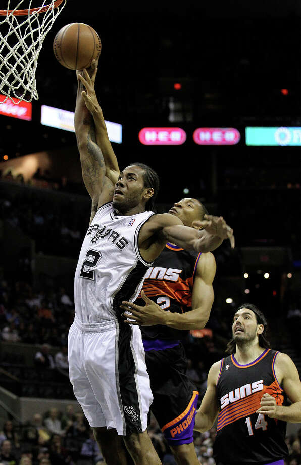 Spurs' Kawhi Leonard (02) gets fouled on a fast break by Phoenix Suns' Wesley Johnson (02) in the first half at the AT&T Center on Wednesday, Feb. 27, 2013. Photo: Kin Man Hui, San Antonio Express-News / © 2012 San Antonio Express-News