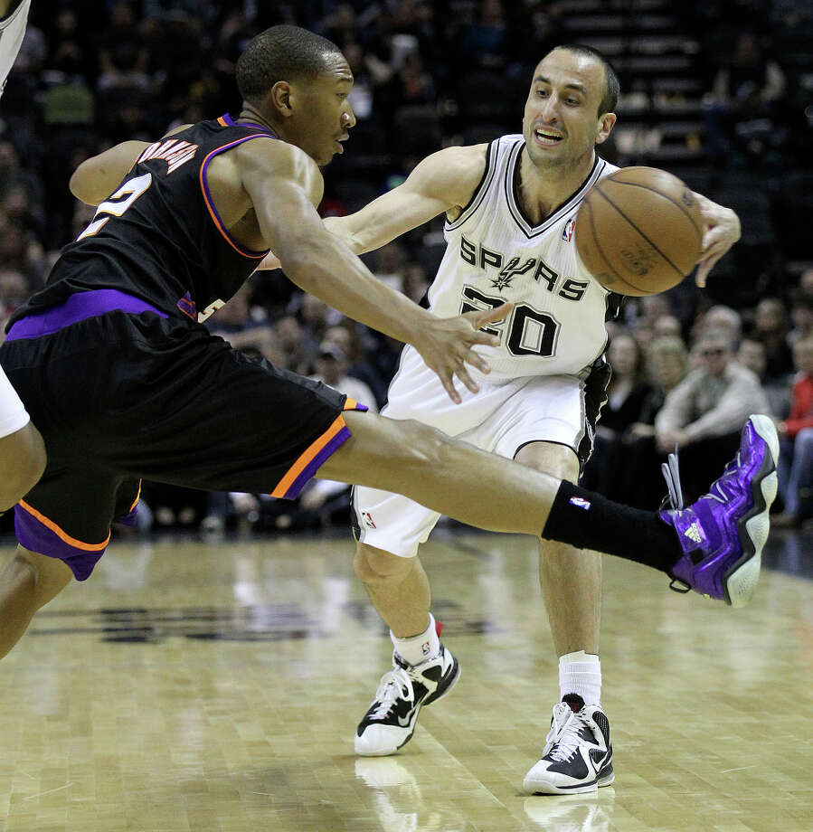 Spurs' Manu Ginobili (20) attempts a pass around Phoenix Suns' Wesley Johnson (02) in the first half at the AT&T Center on Wednesday, Feb. 27, 2013. Photo: Kin Man Hui, San Antonio Express-News / © 2012 San Antonio Express-News