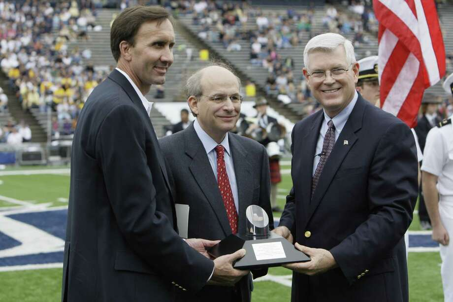 Congressman Pete Olson, left, Rice president David Leebron, and  Johnson Space Center director Mike Coats, right, with moon rock encased in an award ready during presentation onto field for ceremony to  give the award to Rice during halftime of Rice-Navy game Saturday, Oct. 10, 2009, in Houston.  Rice President David Leebron accepted the moon rock and award from Johnson Space Center director Mike Coats on behalf of President John F. Kennedy's family during halftime Saturday, cementing a relationship that began on Sept. 12, 1962, when Kennedy kicked off the race to the moon in a speech at Rice. NASA honored Kennedy's vision with an Ambassador of Exploration Award last summer, 40 years after the Apollo 11 landing on the moon, and the Kennedy family asked that Rice display the award. Both will go on display at Fondren Library on the Rice campus.  ( Melissa Phillip / Chronicle ) Photo: Melissa Phillip, Houston Chronicle / Houston Chronicle