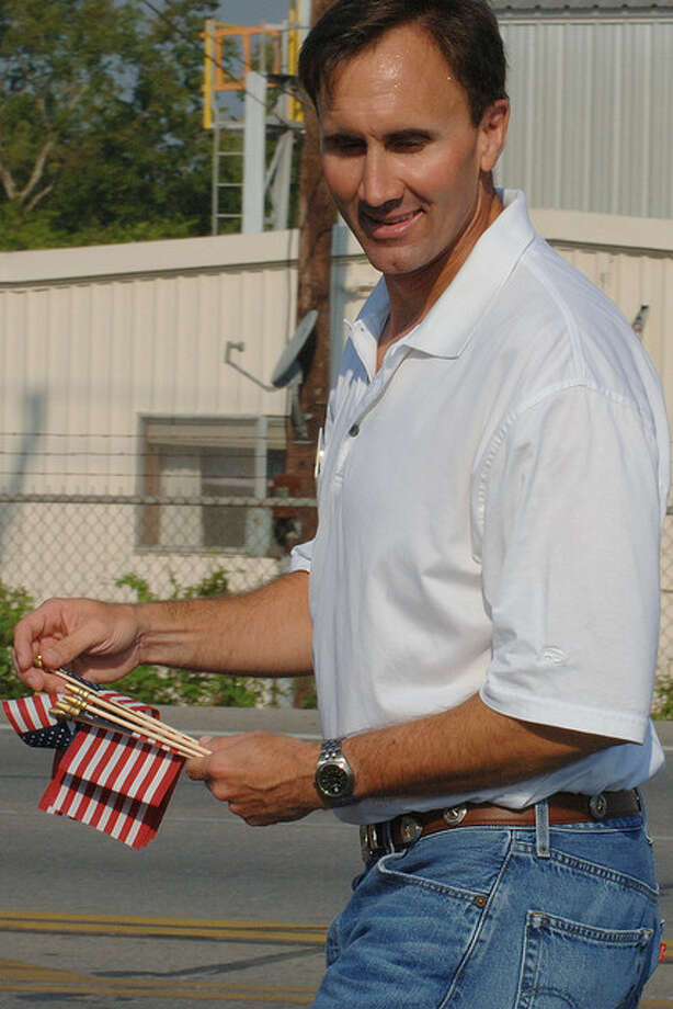 Republican Congressional (TX-22) candidate Pete Olson hands out flags to parade viewers.
