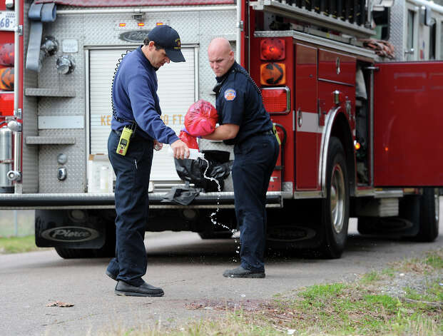 Beaumont firefighters clean up blood stains Thursday morning from the city's first homicide of the year. Lorenzo Simon was shot and killed Wednesday night on the 10000 block of Dusty Lane. Police are investigating.  Photo taken Thursday, February 2013 Guiseppe Barranco/The Enterprise Photo: Guiseppe Barranco, STAFF PHOTOGRAPHER / The Beaumont Enterprise