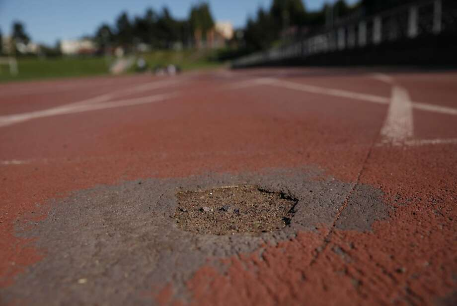 Holes mar the running track near where 100-meter dash starting blocks are set at Kezar Stadium in S.F. Photo: Lea Suzuki, The Chronicle