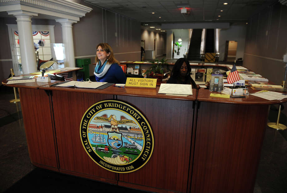Receptionist Carmela DiSanto, left, greets visitors at the front desk of the Margaret E. Morton Government Center on Broad Street in downtown Bridgeport on Thursday, February 28, 2013. Visitors are asked to sign in and have a seat while the person they are visiting is contacted. Photo: Brian A. Pounds / Connecticut Post