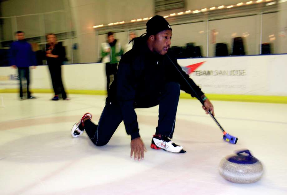 In this Nov. 3, 2009, file photo, San Francisco 49ers football player Vernon Davis learns the game of curling with members of the San Francisco Bay Area Curling Club, in San Jose. Davis is headed to his first Pro Bowl and his first Olympics, too. The 49ers tight end will be an honorary captain for the U.S. men's curling team next month at the Vancouver Olympics. Photo: Marcio Jose Sanchez, AP / AP