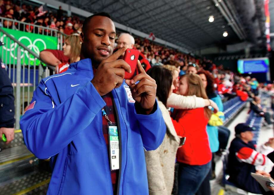 San Francisco 49ers tight end and honorary captain of the United States curling team Vernon Davis snaps a photo before the curling match against France at the Winter Olympic Games in Vancouver, British Columbia, on Friday, Feb. 19, 2010. The United States beat France 4-3. Photo: Paul Chinn, The Chronicle / SFC