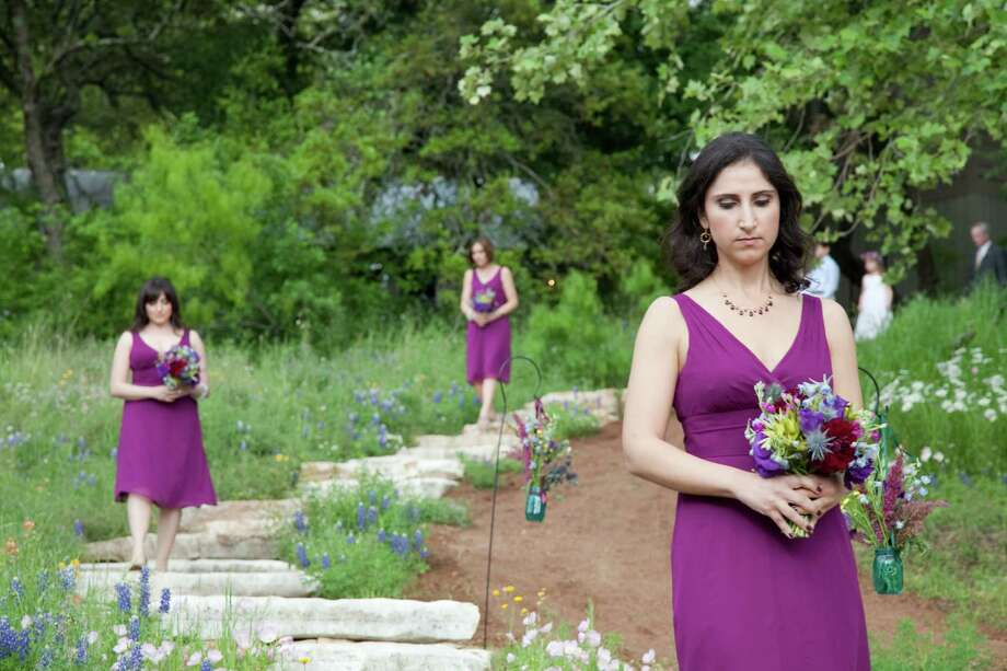 Bridesmaids follow a stepping stone path to one of the riverside ceremony spaces at The Retreat at Balcones Springs. Photo: Stella And Leon Alesi, Photographer
