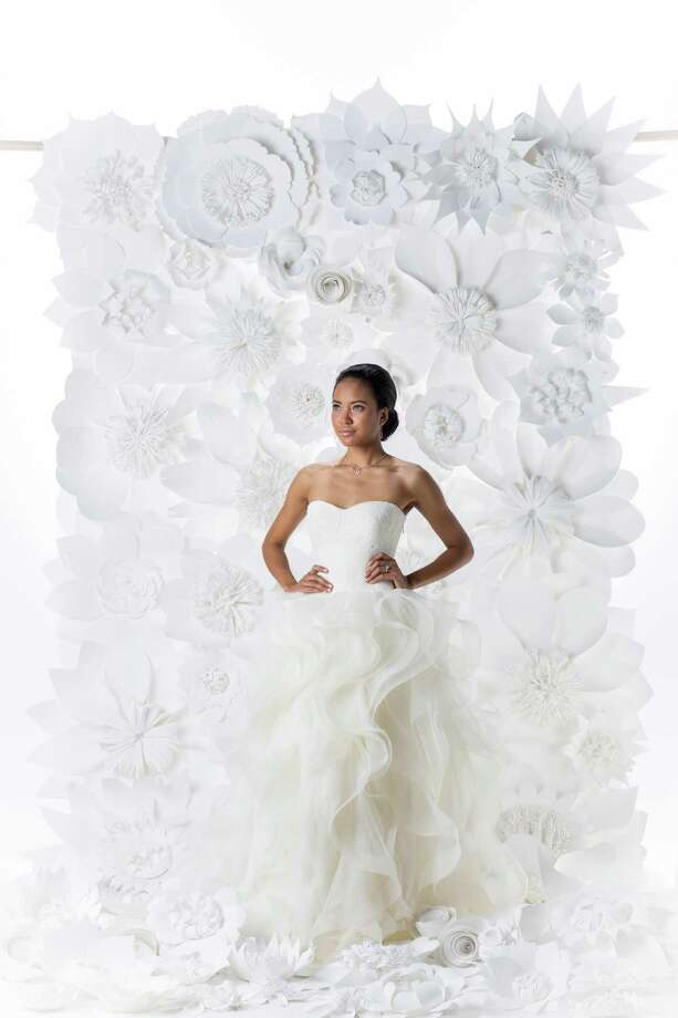 "Josephina Chhin of Neal Hamil Models is wearing a Vera Wang ""Katherina"" dress, $9,500, from Casa de Novia Bridal Couture, with jewelry from I.W. Marks. Makeup and hair by Tree Vaello. Floral backdrop by Balushka, balushka.com. Photo: Michael Paulsen, Staff / © 2013 Houston Chronicle"