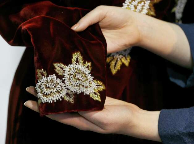 Beading detail is shown on a Catherine Walker burgundy velvet sheath with embroidered tailcoat worn for the State visit to Korea in 1992 by Britain's Princess Diana. The dress is estimated to bring in $62,000-93,000. Photo: Kirsty Wigglesworth