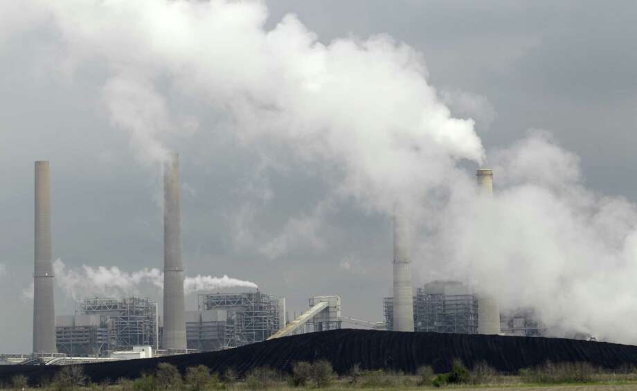 Exhaust rises from smokestacks in front of piles of coal at NRG Energy's W.A. Parish Electric Generating Station in Thompsons. Photo: File Photo, Associated Press