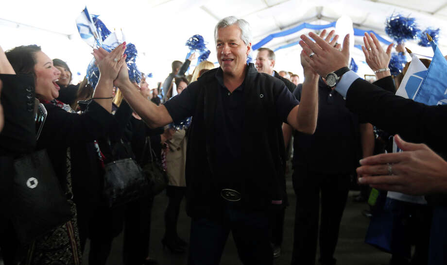Jamie Dimon, chairman and CEO of the nation's largest bank, New York-based JPMorgan Chase & Co., high-fives with some of the 5,000 Chase employees in San Antonio. Dimon met with employees at the Chase Stone Oak Call Center as part of a four-city Texas bus tour. Earlier in the week, the company, which employs more than 259,000 people, announced in New York that it plans to cut costs by reducing mortgage and consumer division workers by 19,000 over the next two years with 4,000 jobs being eliminated this year. Photo: Jerry Lara, San Antonio Express-News / © 2013 San Antonio Express-News