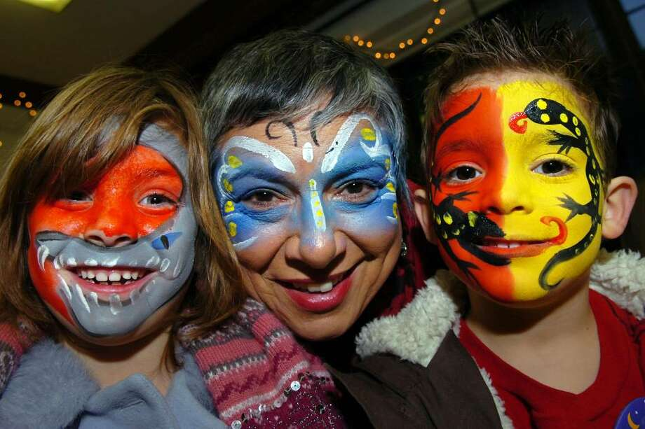 Gloria D'Anna, center, and her twin 5-year old grandchildren Charlotte D'Anna, left, and Oliver D'Anna, right, (all of Westport), pose after getting their faces painted at the First Night Westport 2010 celebration in Westport, Conn. Dec. 31st, 2009. Photo: Ned Gerard / Connecticut Post