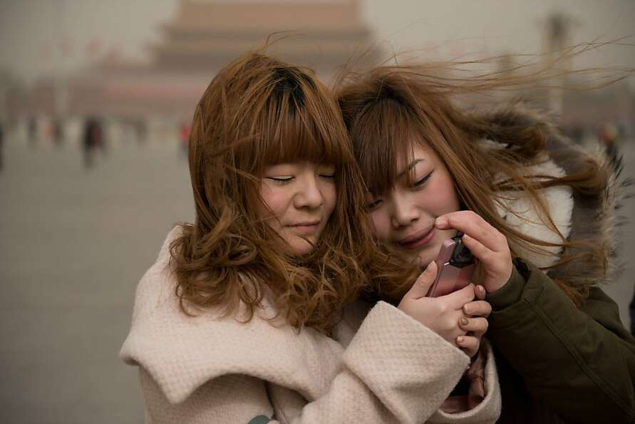 Two women look at a mobile phone as they stand on Tiananmen Square during a sand storm in heavily po