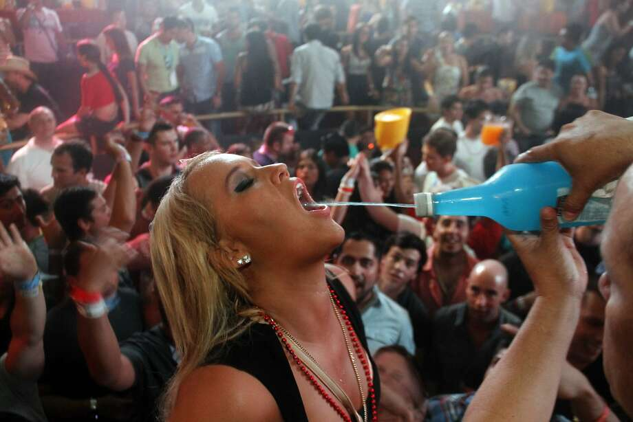 Ready, aim, squirt! At many nightclubs in Cancun, partying college students can get a buzz on without a glass ever touching their lips. Photo: Israel Leal, Associated Press