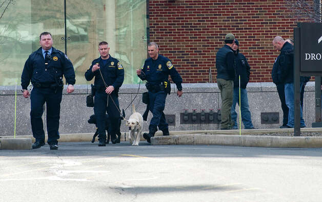 Police officers with dogs inspect Stamford Superior Court on Thursday, February 28, 2013, after a bomb threat was made. Photo: Lindsay Perry / Stamford Advocate