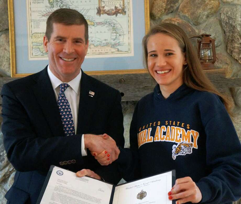 Jim Carrier, a Blue and Gold officer for the United States Naval Academy, stands alongside Staples High senior Emily Troelstra, who is holding her Offer of Appointment from the Naval Academy. Photo: Contributed Photo