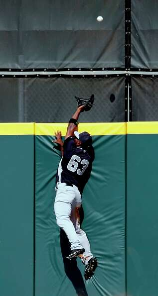 Yankees center fielder Melky Mesa leaps at the wall as he tries to catch a home run hit by Rick Anki