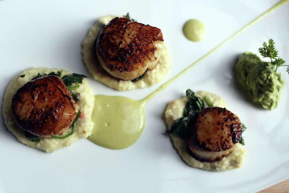 Served on grits with spinach and avocado mousse, the mollusks are sweet and succulent. Photo: Helen L. Montoya / San Antonio Express-News