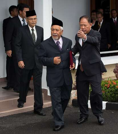 Hassan Taib (C), Chief of Barisan Revolusi Nasional (BRN) holds a document folder as he walks along with other delegates after the signing ceremony of the general consensus document to launch a dialogue process for peace in the border provinces of Southern Thailand, at the Malaysia Police Training Center in Kuala Lumpur on February 28, 2013. Thailand's government on February 28 signed its first-ever agreement with a rebel group in its Muslim-majority south, pledging to work toward peace talks aimed at ending a festering insurgency. AFP PHOTO / MOHD RASFANMOHD RASFAN/AFP/Getty Images Photo: Mohd Rasfan, AFP/Getty Images