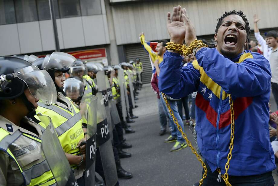 Students demosntrate with chains in front of policemen in Caracas on February 26, 2013. The sudents believe that the government is not saying the truth about Venezuelan President Hugo Chavez's health. Chavez, whose inauguration was delayed due to cancer treatment, will decide himself when he is ready to be sworn in to office, the National Assembly's leader said Monday. AFP PHOTO/Leo RAMIREZLEO RAMIREZ/AFP/Getty Images Photo: Leo Ramirez, AFP/Getty Images