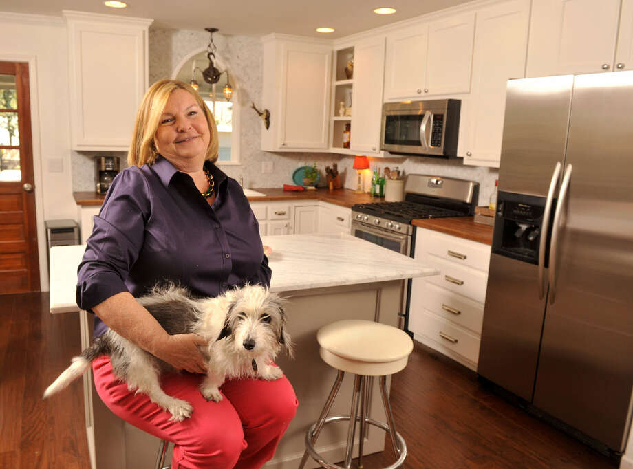 Cheryl Hansen Gordon sits with her dog, Penny, in her New Braunfels kitchen. Gordon used her experience renovating houses — her current home is her 10th project — to revamp her kitchen. Photo: Photos By Robin Jerstad / For The Express-News