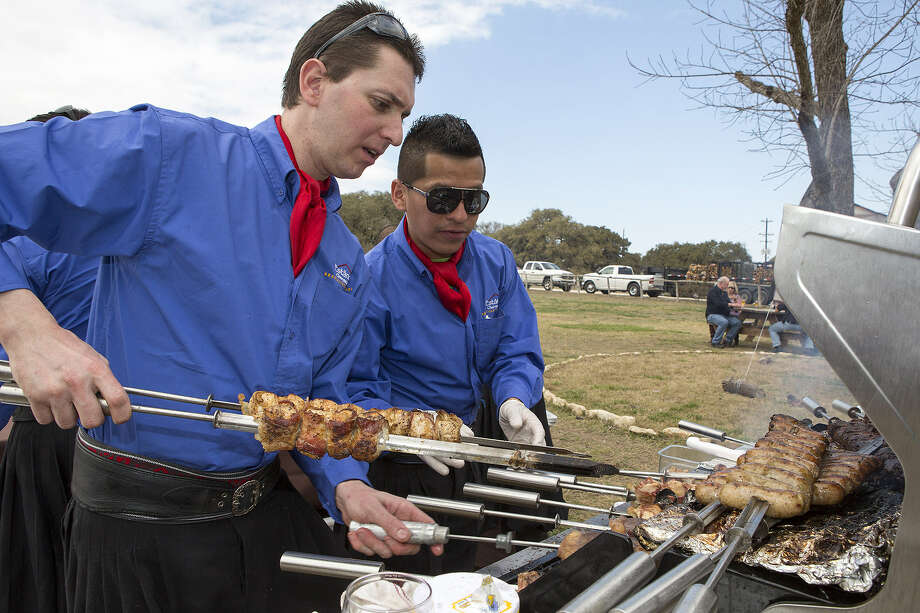 Marcelo Coutinho (left) and Daniel Ybarra work the grill  at the Cowboys + Gauchos event in Driftwood.  The Wine & Food Foundation of Texas hosted the event. Photo: Photos By Michael Miller / For The Express-News