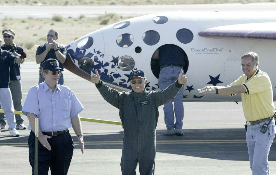Burt Rutan, Paul Allen and Michael W. Melvill, the pilot of the SpaceShipOne craft wave to the crowd during celebrations in Mojave after they become the first commercial craft in space. Photo: Chris Weeks, / / WireImage