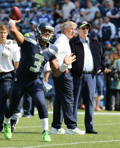 Paul Allen talks with Seahawks head coach Pete Carroll as quarterback Russell Wilson warms up prior