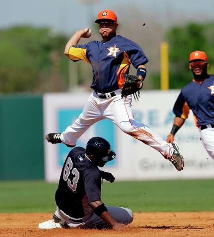 Astros 7, Yankees 6Astros second baseman Jose Altuve, top, leaps over the Yankees' Melky Mesa as he throws to first to complete a double play during the second inning on Thursday in Kissimmee, Fla. Photo: David J. Phillip