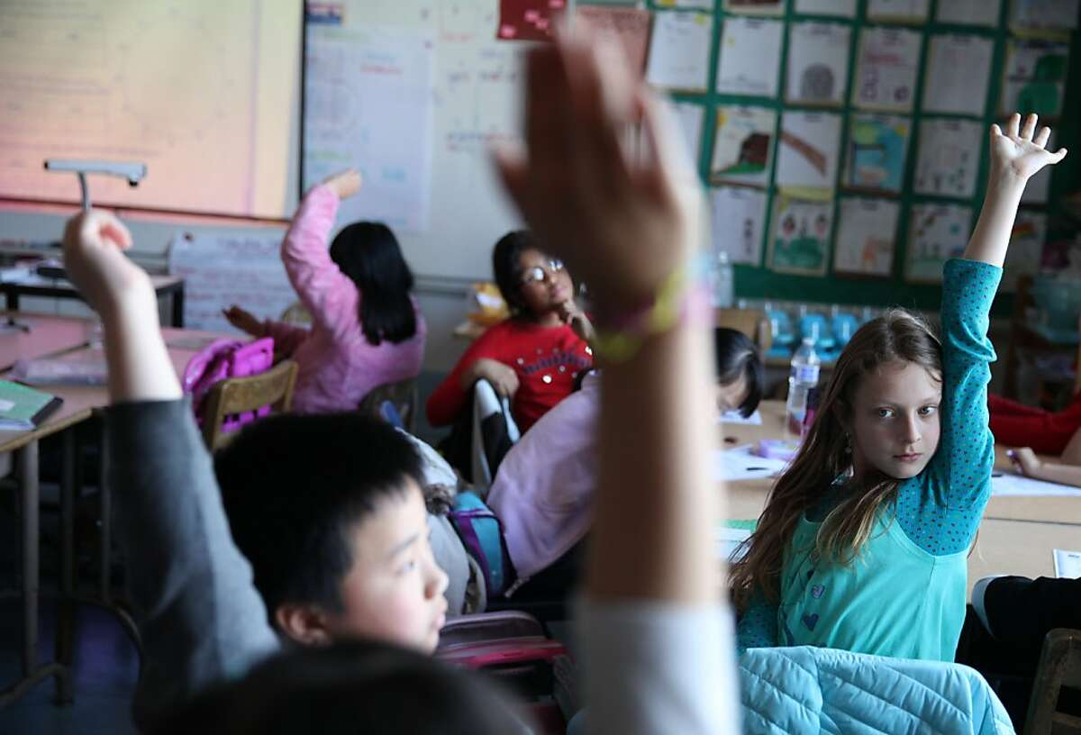Charles Wong, 9 (l to r foreground) and Ariel Hendel,10, raise their hands during class at Spring Valley Science School on Thursday, February 28, 2013 in San Francisco, Calif.