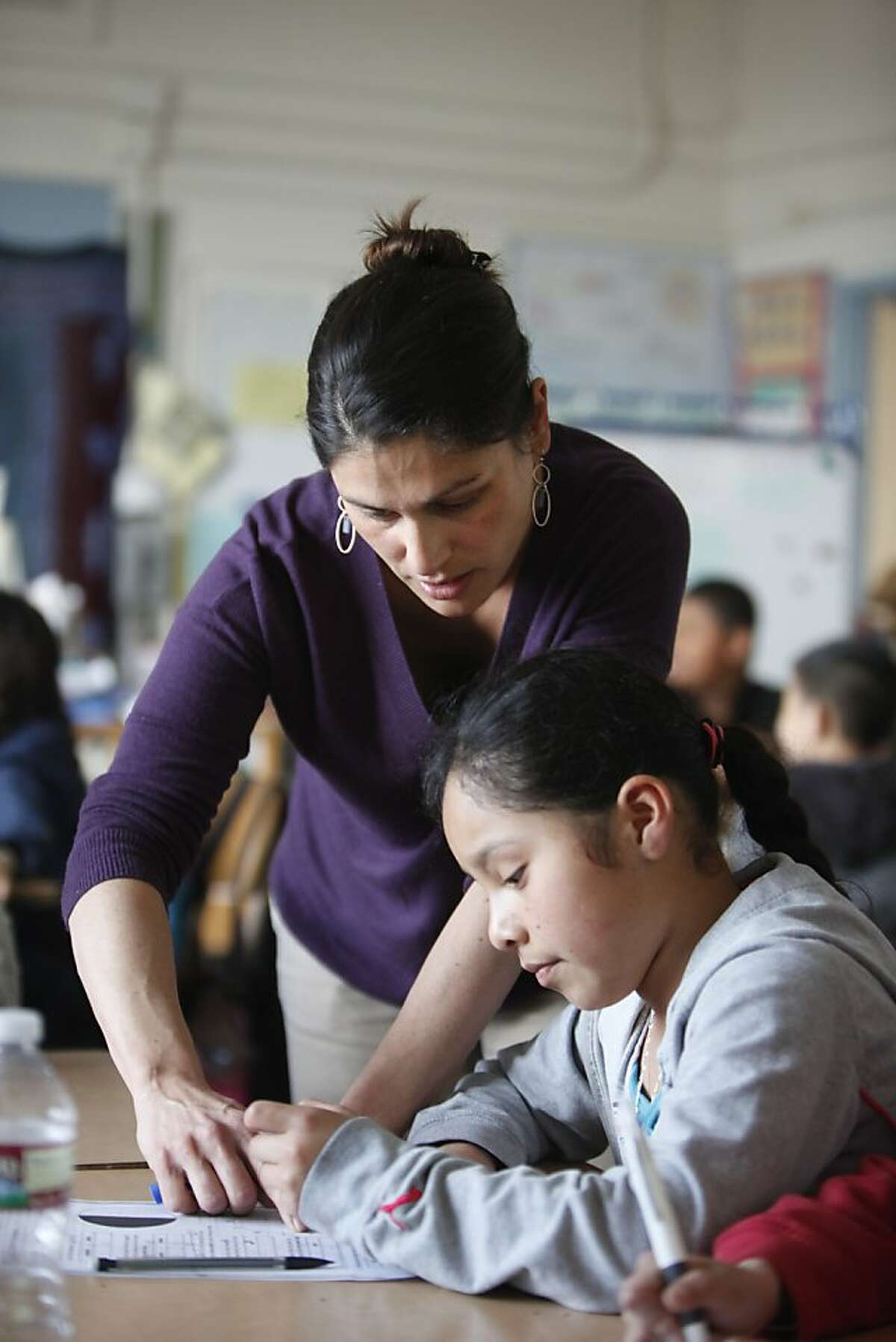 Teacher Jessica Chiarchiaro (l to r) helps fourth grader Daniela Garcia, 10, with a class assignment at Spring Valley Science School on Thursday, February 28, 2013 in San Francisco, Calif.