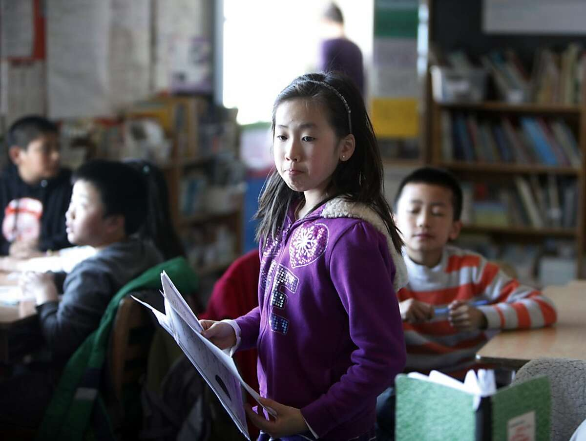 Fourth grader Jasmine Chu, 9, hands out papers during class at Spring Valley Science School on Thursday, February 28, 2013 in San Francisco, Calif.