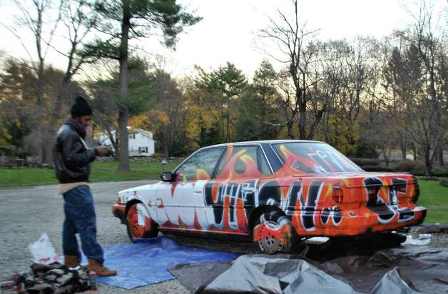 Norwalk artist Jahmane West painted a junk car at Beechwood Arts NYC 1970's Downtown Birthday Bash. Photo: Contributed Photo / Connecticut Post Contributed