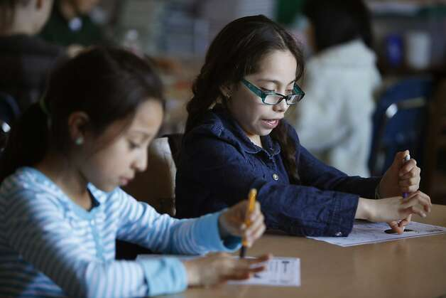 Fourth graders Giselle Jacobo-Gomez, 9 (l to r), and Aislinn Cruz, 10,  work on a class assignment at Spring Valley Science School on Thursday, February 28, 2013 in San Francisco, Calif. Photo: Lea Suzuki, The Chronicle
