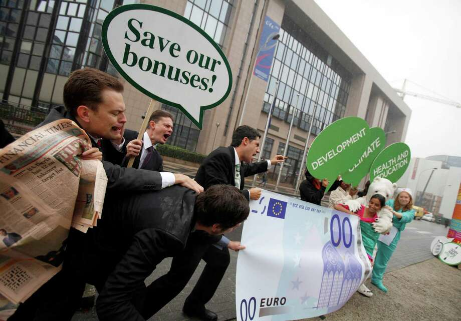File - In this Sept. 7, 2010 file photo, members of Oxfam are dressed as bankers during a demonstration outside of a meeting of EU finance ministers at the EU Council building in Brussels. Top European Union officials late Wednesday, Feb. 27, 2013 struck an agreement on a package of financial laws that includes capping bankers' bonus payments at a maximum of one year's base salary. The bonuses will only be allowed to reach twice the annual fixed salary if a large majority of a bank's shareholders agrees. (AP Photo/Virginia Mayo, File) Photo: Virginia Mayo