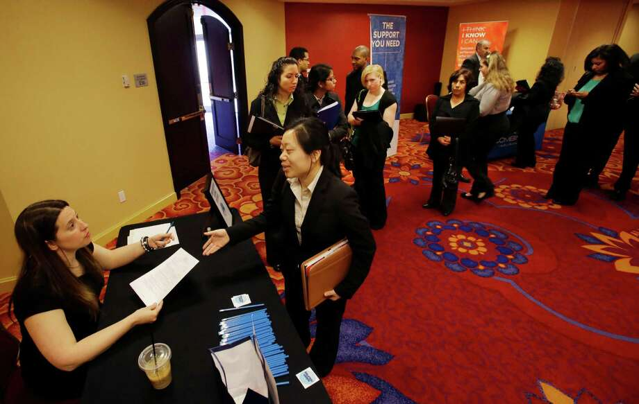 In this Tuesday, Feb. 26, 2013, photo, a line of people wait, as Neely Raffellini, left, helps job seekers revise their resumes during the Edison Career Fair job fair in the Iselin section of Woodbridge Township, N.J. The number of Americans seeking unemployment aid fell 22,000 last week to a seasonally adjusted 344,000, evidence that the job market may be picking up. (AP Photo/Mel Evans) Photo: Mel Evans