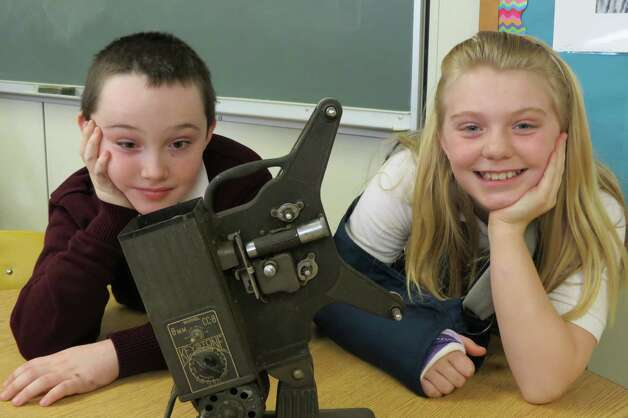 "Fifth graders, Gabe and Lizzie are intrigued by the old-fashioned projector being used in a display at All Saints Catholic Academy's ""Stepping Out ... An Evening of Old Hollywood"" benefit March 16 at the Italian American Community Center. The projector will be on display with other items from that era during the evening featuring dinner, wine tasting, a silent auction, as well as musical entertainment by Rosanne Hargrave and Joe Kriss.  More information is available at All Saints Catholic Academy at 438-0066 or see      http://www.ascaalbany.org/SteppingOut.aspx (Karen Reilly)"