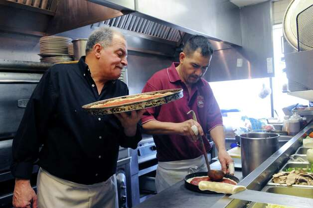 Magdi Alawadi, left, and Manuel Sosa finishes a pizza at Famous Greek Kitchen, at Byram, Conn., Thursday, Feb. 21, 2013. The family-run restaurant which started over 30 years ago under a different name, is being reopened by the children of the original owners, with new décor and menu. Photo: Helen Neafsey / Greenwich Time