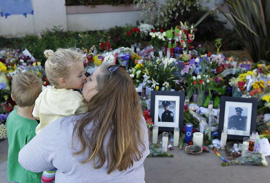 Chris Breeden visits the slain officers' memorial at Santa Cruz police headquarters with her children James, 5, and Hollie, 3. Photo: Paul Chinn, The Chronicle
