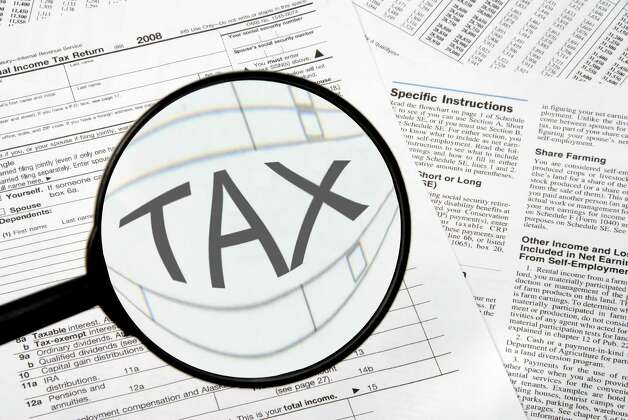 Federal tax forms under a magnifying glass. Photo: Robert Byron / Rob Byron - Fotolia