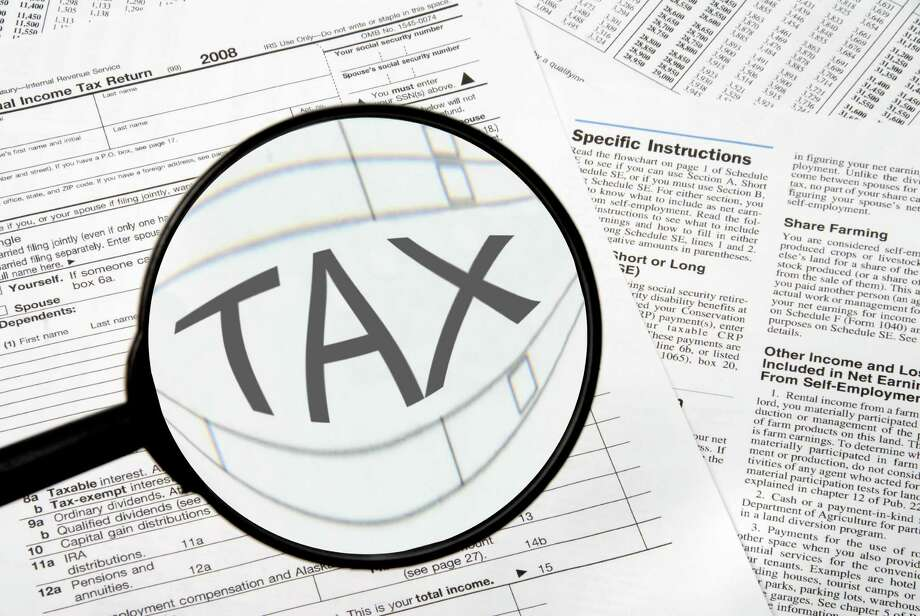 Federal tax forms under a magnifying glass. Photo: Robert Byron / Rob Byron - Fotolia