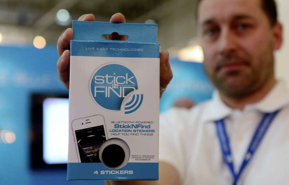 A man holds the Stick-N-Find product at the Mobile World Congress, the world's largest mobile phone trade show, in Barcelona, Spain Wednesday Feb. 27, 2013. Stick-N-Find Technologies, wants to give people a way to find things, by using a new radio technology known as Bluetooth Low Energy, which drastically reduces the power consumption of a transmitting device. (AP Photo/Manu Fernandez) Photo: Manu Fernandez
