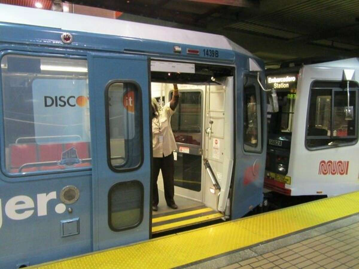A Muni operator examines a Metro car where a door was knocked off while it drove through a tunnel Thursday afternoon.