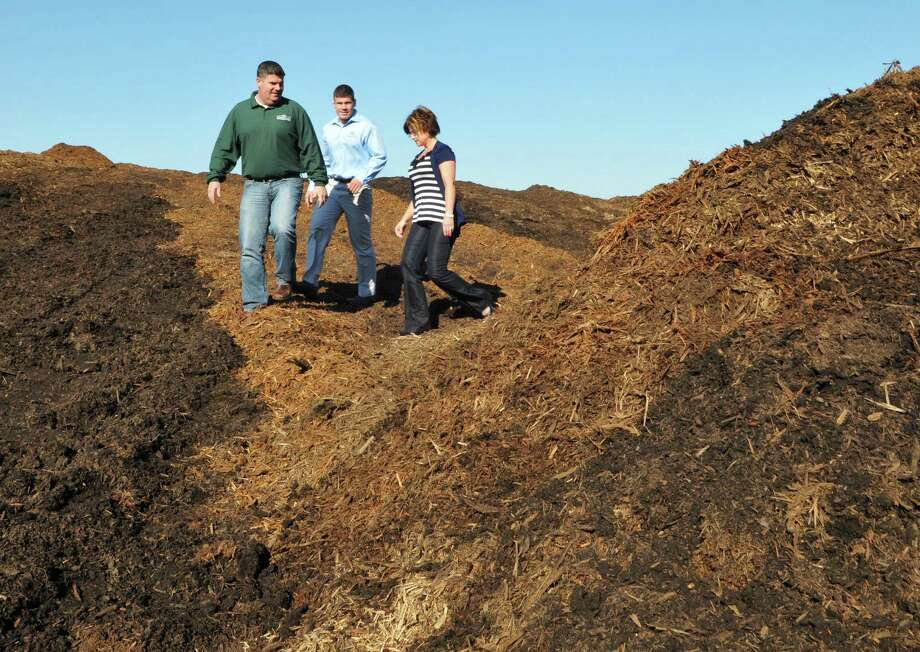 Siblings and co owners, from left,  Sean, Brendan and Shannon Gallivan walk through mountains of pine bark mulch at Gallivan Companies in Troy Wednesday Nov. 2, 2011.   (John Carl D'Annibale / Times Union) Photo: John Carl D'Annibale / 00015246A