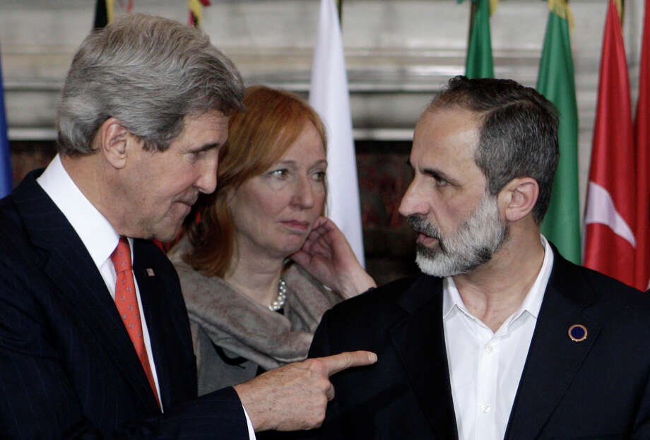 U.S. Secretary of State John Kerry, left, talks to Syrian opposition coalition leader Mouaz al-Khatib on Thursday at a conference on Syria held in Rome. Photo: Riccardo De Luca, STR / AP