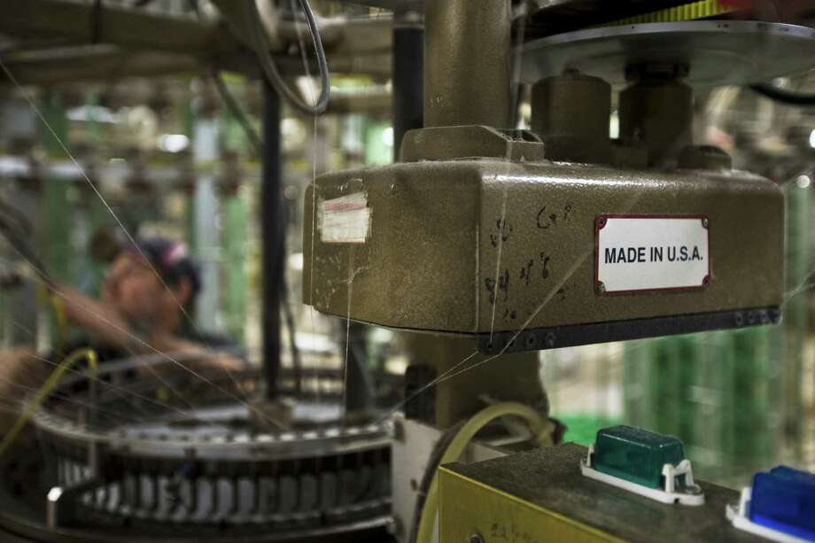 "A machine is affixed with a ""Made in the U.S.A."" plate at the FesslerUSA apparel manufacture in Orwigsburg, Pa. The U.S. economy barely grew from October through December, the 0.1 percent increase the weakest performance in nearly two years. Photo: Associated Press File Photo"