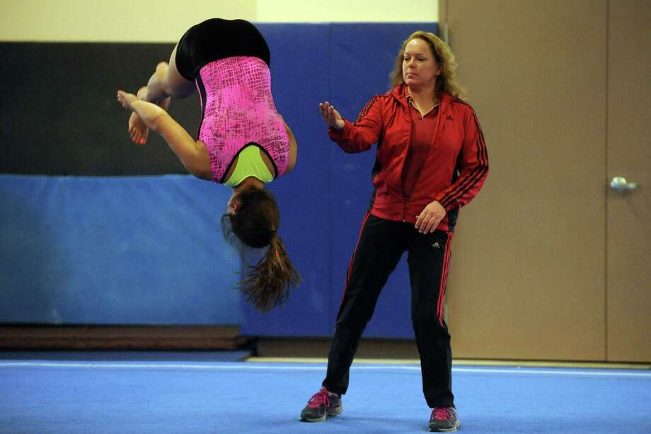 Guilderland High School coach Brenda Goodknight assists as gymnastics athlete Hailey Marini practices with the Section II team on Tuesday Feb. 26, 2013 in Saratoga Springs, N.Y. (Michael P. Farrell/Times Union) Photo: Michael P. Farrell