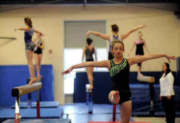 Saratoga High School gymnastics athlete Kelsey Jackowitz, left, practices with the Section II team on Tuesday Feb. 26, 2013 in Saratoga Springs, N.Y. (Michael P. Farrell/Times Union) Photo: Michael P. Farrell