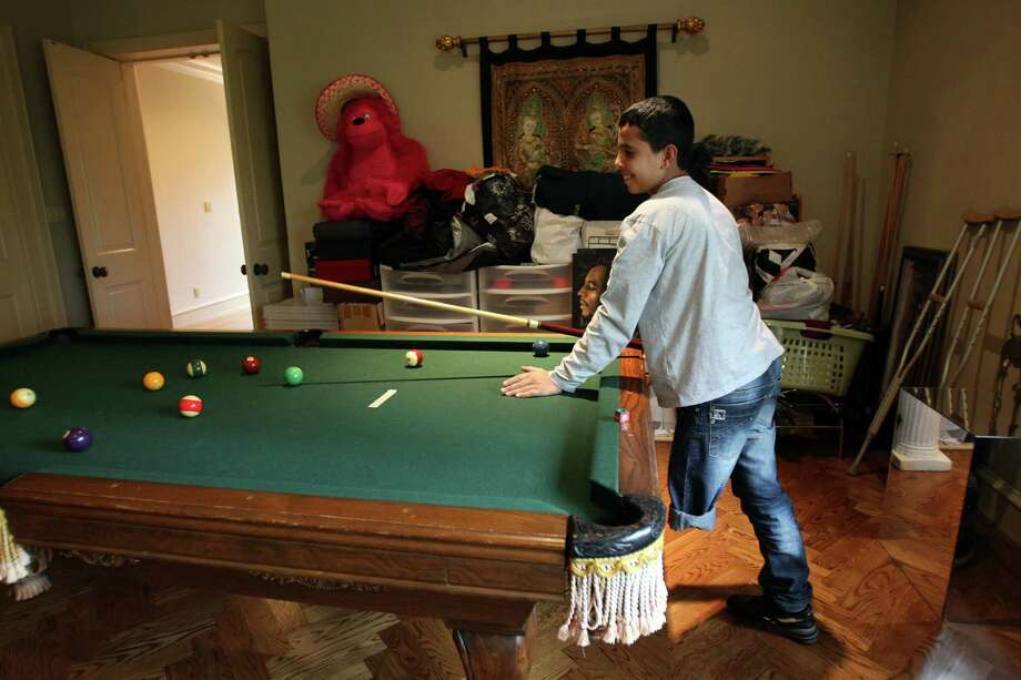 Playing pool is one of Mohammed Jammous' favorite pastimes. Mohammed, who was hurt in the Syrian civil war, will receive a prosthetic leg. Photo: Mayra Beltran, Staff / © 2013 Houston Chronicle
