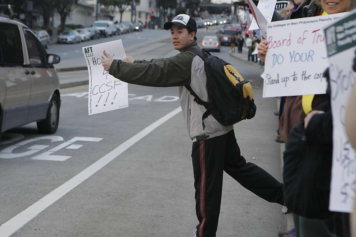"""Alex Huynh holding up a sign as cars drive by during the rally on February 28, 2013 at City College of SF in San Francisco, Calif. Faculty are furious about stalled contract negotiations, which call for multi-year paycuts to deal with budget problems at the school. The faculty are doing """"Human Billboarding"""" and a rally at Ocean Ave."""